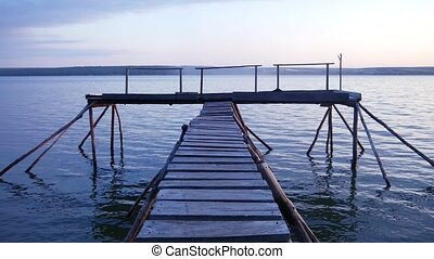 Wooden pier on the lake shore. Twilight. Peace and tranquility