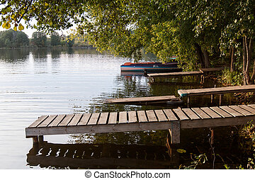 wooden pier on the lake side view with green trees. summer day