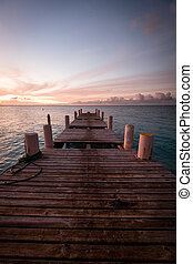 Wooden pier on the sea during sunset. Beautiful orange purple sk
