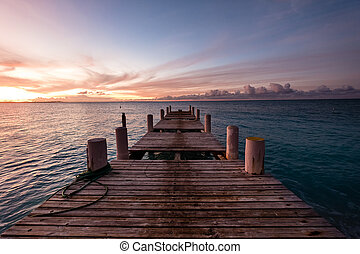 Wooden pier on the sea during sunset. Beautiful orange purple skies reflecting on the ocean. Grace Bay Beach, Providenciales, Turks and Caicos.