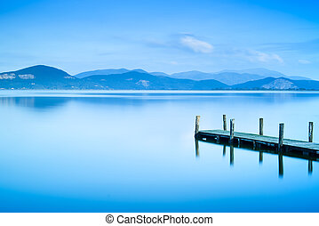 Wooden pier or jetty and on a blue lake sunset and cloudy sky reflection on water. Long exposure, Versilia Massaciuccoli Lake, Tuscany, Italy.