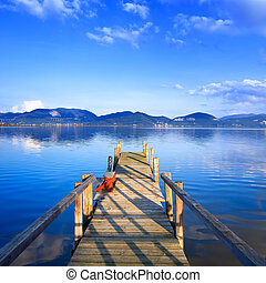 Wooden pier or jetty on a blue lake sunset and cloudy sky reflection on water. Long exposure, Versilia Massaciuccoli Lake, Tuscany, Italy.