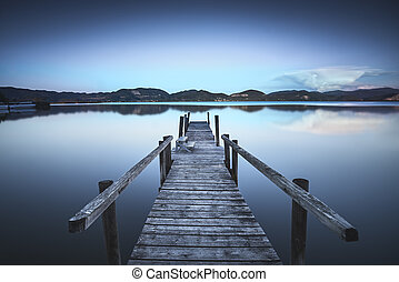 Wooden pier or jetty on a blue lake sunset and sky reflection on water. Versilia Tuscany, Italy