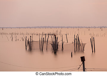 Wooden pier or jetty remains on a blue lake sunset and cloudy sky reflection on water.