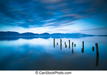 Wooden pier or jetty remains on blue lake sunset and sky reflection water. Long exposure, Versilia Massaciuccoli, Tuscany, Italy.