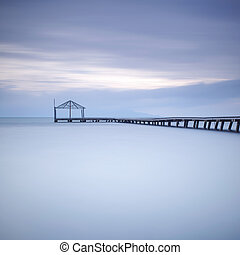 Wooden pier or jetty silhouette and blue ocean on sunset -...