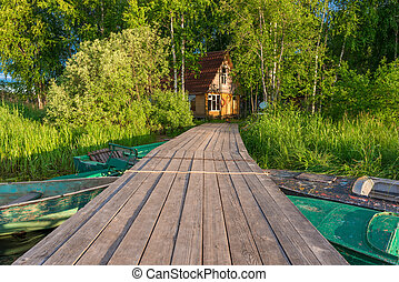 wooden pier to the fisherman's house on the shore of a beautiful lake