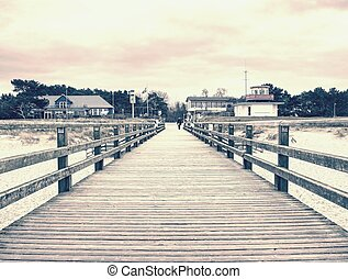 Wooden pier turquoise sea water sunny day, long beach