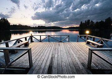 Wooden pier with lanterns leaving the lake