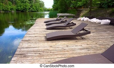 Wooden pier with loungers and relax pillows. Summer river...
