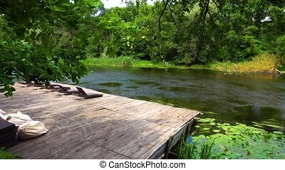 Wooden pier with loungers and river. Summer tranquil place