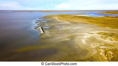 Wooden pier with tourist footbridge and lookout point on sandbank near shallow Venetian lagoon under bright sky aerial motion