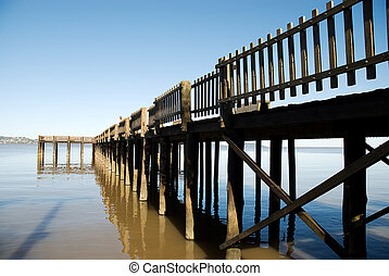 Wooden Pier - Wooden pier with blue sky over brown lake,...