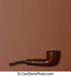 Wooden pipe against brown backgound with empty space above