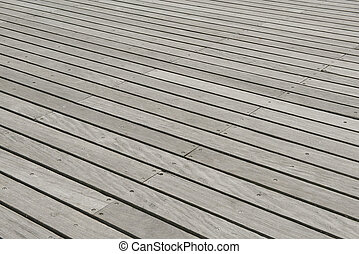 Wooden plank floor of a pier with the lines diagonal
