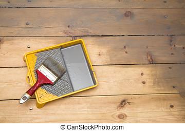 wooden plank floor varnishing. gray varnish and paintbrush in tray