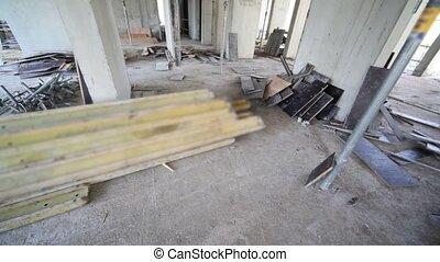 Wooden planks lies in unfinished room, metal struts prop up...