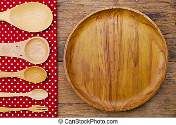 Wooden plate, tablecloth, spoon, fork on old table background