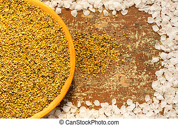 Wooden plate with bee pollen on rustic table