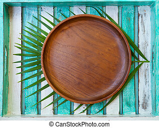 Wooden plate with palm leaf on colorful background. Copy space. Top view.
