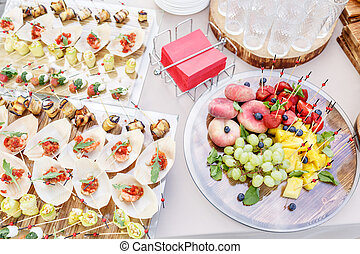Wooden plate with sliced fruits and berries on a buffet table. and other snacks and canapes. Summer party outdoor. Horizontal photo