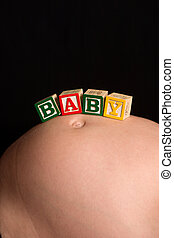 Wooden play blocks spelling the word baby - Pregnant belly...