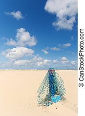 Wooden pole with fishing net at the beach