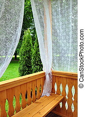 Wooden porch with lace curtains and garden view