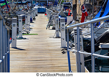Wooden port bridge with chargers to yachts in Puerto De Mogan on Gran Canaria.