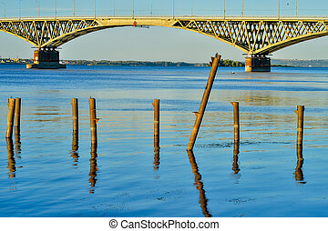 Wooden posts for the berth of boats and boats on the reservoir in the background of the bridge