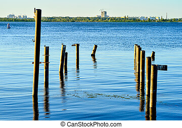 Wooden posts for the berth of boats and boats on the reservoir