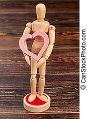 Wooden puppet holding pink heart.