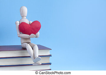 Wooden puppet human siting on a pile of books with red plush heart in hands