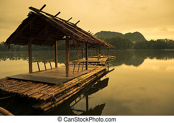 wooden raft on water before sunrise