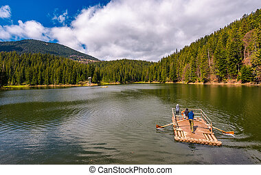 wooden raft with tourists on Synevyr lake - Synevyr, Ukraine...