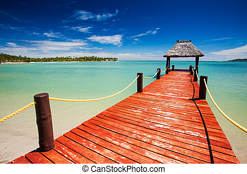 Wooden red jetty extending to tropical green lagoon