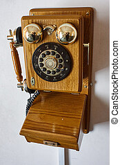Wooden retro phone on a red wall.