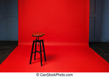 Wooden retro stool on red background. No one, free space on...
