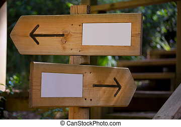Wooden road sign with two opposite arrow directions