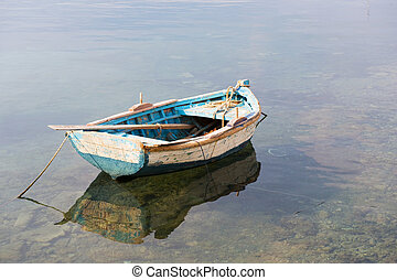 Wooden blue row boat in calm water