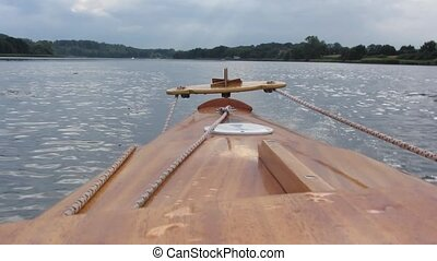 Wooden rowboat tail with rudder moving on river while people...