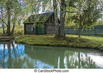 Wooden Russian bathhouse on the shore of a small pond in the village of Vyatskoye, Russia.