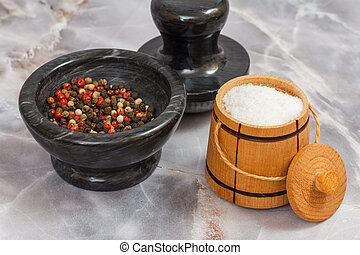 Wooden salt cellar and stone bowl with peppercorn on gray background.
