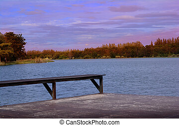 wooden seat at riverside with blue sky and trees