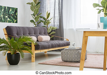 Wooden settee in bright interior - Patterned pouf and palm...