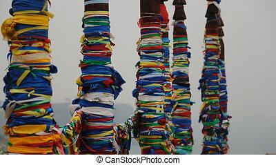 Wooden shaman totems with ribbons near holy cape Burkhan on...