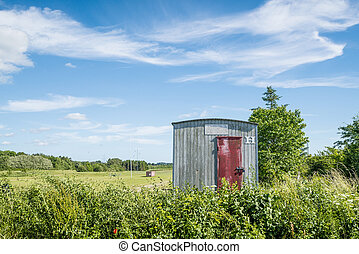 Wooden shed on a rural field