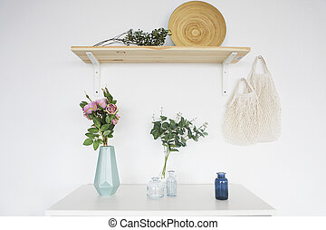 Wooden shelf and white commode on light wall background