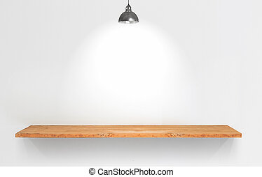 Wooden shelf with lamp on white wall.