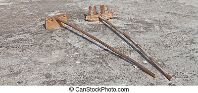 Wooden shovel and rake on the ground